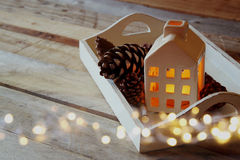 Photo of decorative house and pine cones next to gold garland lights on wooden background. copy space. retro filtered Royalty Free Stock Photography