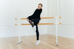 Photo of delighted red haired woman keeps hand on knee, raises one leg, wears black suit and white sneakers, stands near ballet stock images