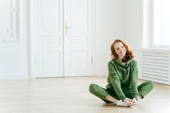Photo of delighted redhead female sits on lotus pose, wears tracksuit, being in good body shape, has curly ginger hair, poses on royalty free stock image