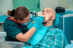 Photo dentist treating teeth to the patient Stock Photography
