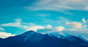 Photo depicting a beautiful moody frosty landscape European alpi. Ne mountains with snow peaks on a blue sky background Royalty Free Stock Images