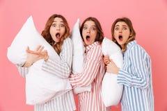 Photo des amies 20s dans l'usage à la maison tenant des oreillers et des expres Image stock