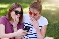 Photo des belles filles choquées, soeurs avec des expressions du visage étonnées, étudiants s'asseyant en parc dehors sur l'herbe photographie stock libre de droits