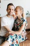 Photo des couples dans l'amour se reposant sur le sofa en cuir Images stock
