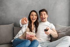 Photo des couples de sourire se reposant sur le sofa à la maison et se dirigeant à Photo stock