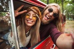 Photo des couples hippies européens souriant, et montrant le signe de paix photos stock