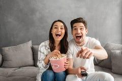 Photo des couples joyeux souriant et se reposant sur le sofa à la maison avec Image libre de droits