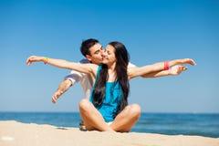 Photo des couples mignons se reposant sur la plage et embrassant sur gagné Photos stock