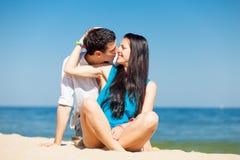 Photo des couples mignons se reposant sur la plage et embrassant sur gagné Photo stock