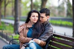 Photo des couples mignons se reposant sur le banc et étreignant sur gagné Photo stock