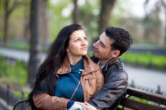 Photo des couples mignons se reposant sur le banc et étreignant sur gagné Photo libre de droits