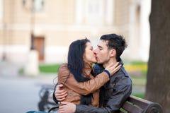 Photo des couples mignons se reposant sur le banc et embrassant sur gagné Images libres de droits