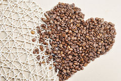 Photo des grains de café en forme de coeur sur le fond beige Photographie stock