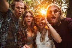 Photo des hommes et des femmes gais de hippies, souriant et prenant l'individu image stock