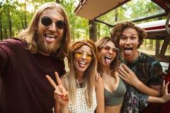 Photo des hommes et des femmes hippies joyeux de personnes, prenant le selfie en FO photos stock