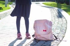 Photo des jambes du ` un s de fille dans une jupe foncée avec un sac à dos rose sur le trottoir Photographie stock libre de droits