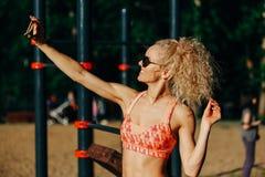 Photo des lunettes de soleil de port de sourire de femme de sports faisant le selfie dedans photos stock