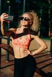 Photo des lunettes de soleil de port de sourire de femme de sports faisant le selfie dedans photo libre de droits