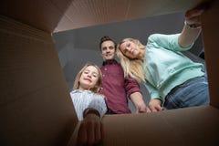 Photo des parents et de la fille regardant à l'intérieur de la boîte en carton photos stock