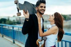 Photo des planches à roulettes de transport de jeunes couples attrayants images stock