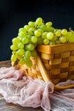 Photo des raisins verts dans la boîte en bois, sur le tissu Photo stock