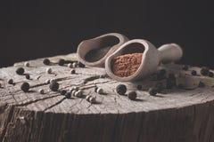 Photo des variétés de poivre sec sur le tronçon en bois et dedans en épice en bois de pelle Photos stock