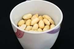 Detail of delicious peanuts in white cup. Photo of Detail of delicious peanuts in white up stock photography