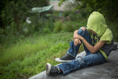 Photo dirty homeless boy with torn jeans. A homeless boy sits on a bench with her head bowed down, portrait Royalty Free Stock Image