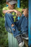 Photo dirty homeless boy with torn jeans. A homeless boy sits on a bench with her head bowed down, portrait Stock Photography