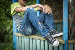 Photo dirty homeless boy with torn jeans. A homeless boy sits on a bench with her head bowed down, portrait Stock Image