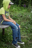 Photo dirty homeless boy with torn jeans. A homeless boy sits on a bench with her head bowed down, portrait Stock Photo