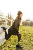 Photo of disabled running woman in sportswear, squatting and stretching prosthetic leg on grass using railing. Photo of disabled running woman in sportswear stock photo