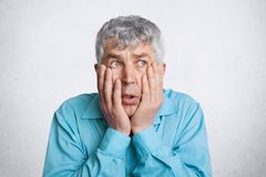Photo of discontent frustrated grey haired male, keeps hands on cheeks, looks desperately somewhere, wears formal blue shirt, isol. Ated over white concrete wall Stock Image