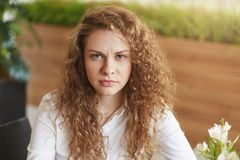 Photo of dissatisfied curly female model frowns face, feels tired and annoyed as waits for someone for long time in cafe, doesn`t. Like when somebody is late Stock Images