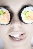 Photo drôle de femme avec le petit pain de sushi sur son oeil photo stock