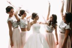 Photo drôle de la jeune mariée et des demoiselles d'honneur dans la chambre Photographie stock