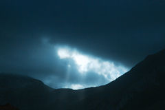 Photo of dramatic rays of light pushing up through clouds Stock Images