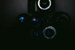 Photo DSLR camera with a set of retro lens and flash on a black background with wood texture Royalty Free Stock Photos