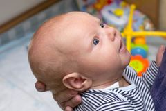 Photo du bébé avec de grands yeux bleus, qui est tenu par la mère images stock