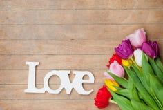 Photo du beau groupe de tulipes colorées et de comprimé en bois Image stock