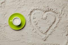 Photo du dessin en forme de coeur et tasse de café sur le sable Image libre de droits