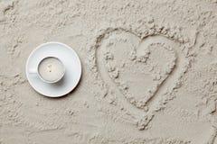 Photo du dessin en forme de coeur et tasse de café sur le sable Images libres de droits