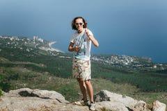 Photo du jeune homme drôle bel se tenant au-dessus des montagnes et regardant l'appareil-photo image libre de droits