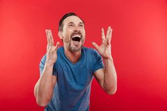 Photo of ecstatic man screaming and rejoicing with gesturing like winner or successful person, isolated over red background. Photo of ecstatic man screaming and stock image
