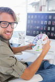 Photo editor holding colour wheel and smiling at camera Royalty Free Stock Image