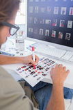 Photo editor making some cuts on the contact sheet. At his desk royalty free stock images