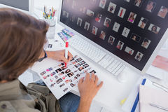 Photo editor making some cuts on contact sheet. At his desk in office royalty free stock photography