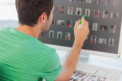 Photo editor pointing at his screen with a green marker Stock Photo