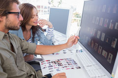 Photo editor pointing at thumbnail on screen with colleague Royalty Free Stock Photography