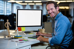 Photo editor smiling while working on graphics tablet royalty free stock images